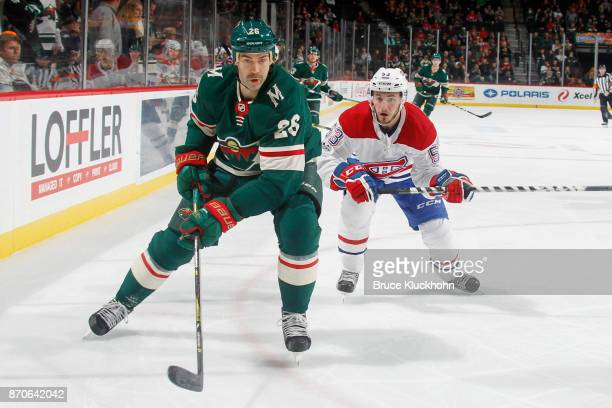 Daniel Winnik of the Minnesota Wild and Victor Mete of the Montreal Canadiens skate to the puck during the game at the Xcel Energy Center on November...