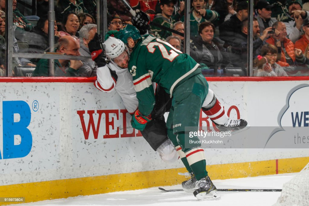 Daniel Winnik #26 of the Minnesota Wild checks Jason Demers #4 of the Arizona Coyotes during the game at the Xcel Energy Center on February 8, 2018 in St. Paul, Minnesota.