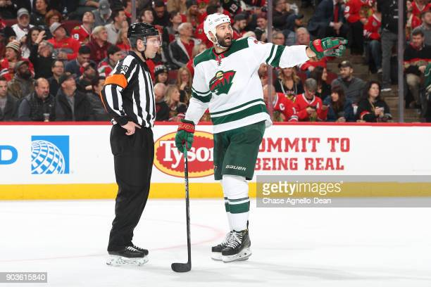 Daniel Winnik of the Minnesota Wild talks with referee Kendrick Nicholson in the second period against the Chicago Blackhawks at the United Center on...