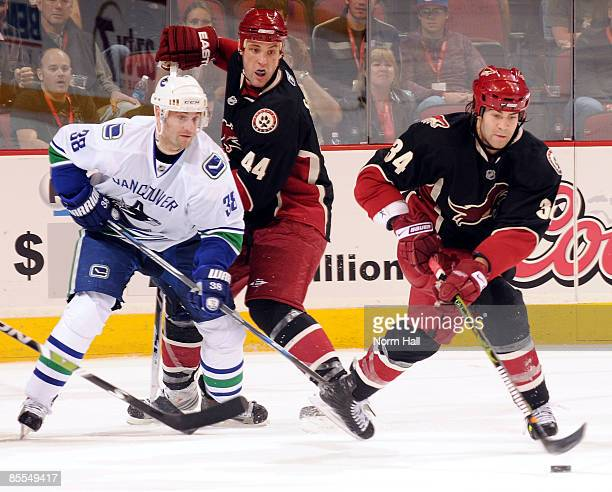 Daniel Winnik of the Phoenix Coyotes goes after a rebound as teammate Kurt Sauer fights for position with Pavol Demitra of the Vancouver Canucks in...