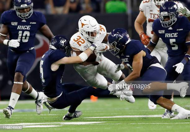 Daniel Young of the Texas Longhorns runs the ball defended by Andrew Bird of the Rice Owls and Naeem Smith in the first half at NRG Stadium on...