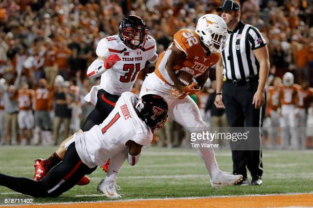 Daniel Young of the Texas Longhorns rushes for a touchdown defended by Jordyn Brooks of the Texas Tech Red Raiders in the second quarter at Darrell K...