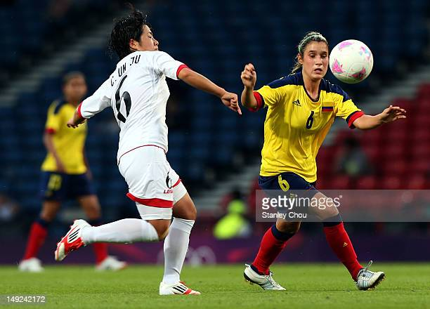Daniela Ariza of Columbia is checked by Choe Un Ju of DPR Korea during the Women's Football first round Group G Match of the London 2012 Olympic...