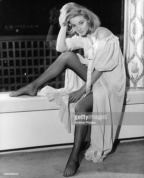 Daniela Bianchi sitting next to a window wearing fishnet stockings in a scene from the film 'James Bond: From Russia With Love', 1963.