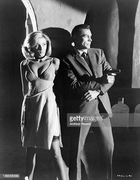 Daniela Bianchi standing next to Sean Connery as he aims a gun away from them in a scene from the film 'James Bond From Russia With Love' 1963