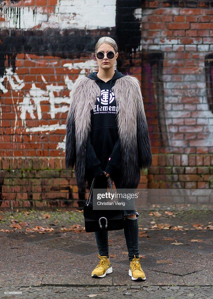 Daniela Breithaupt (@petitefabeli) wearing Nike sneaker, black hoody Element, fake fur coat Unreal Fur, black ripped denim jeans Primark, sunglasses Zaful, black Gucci bag on November 16, 2016 in Berlin, Germany.