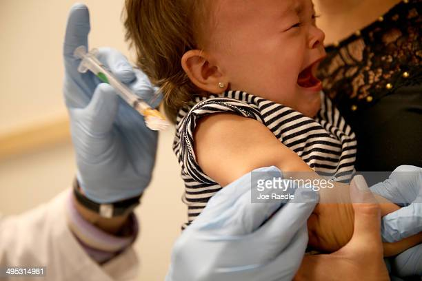 Daniela Chavarriaga holds her daughter Emma Chavarriaga as pediatrician Jose RosaOlivares MD administers a measles vaccination during a visit to the...