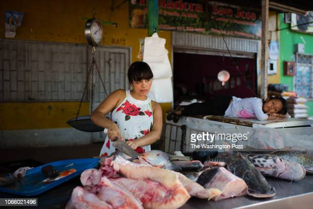 Daniela Giraldo left cuts fish at a morning market while sixyearold Rosal Ximena Castro the daughter of the store owner naps on an ice box San Jose...