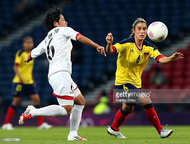 Daniela Motoyo of Columbia is checked by Choe Un Ju of DPR Korea during the Women's Football first round Group G Match of the London 2012 Olympic...