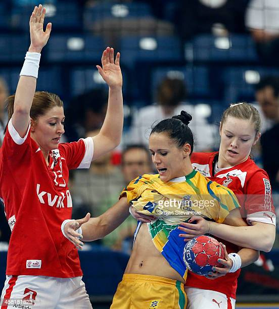 Daniela Piedade of Brazil is challenged by Sofie Johansen and Anne Mette of Denmark during the World Women's Handball Championship 2013 Semi Final...