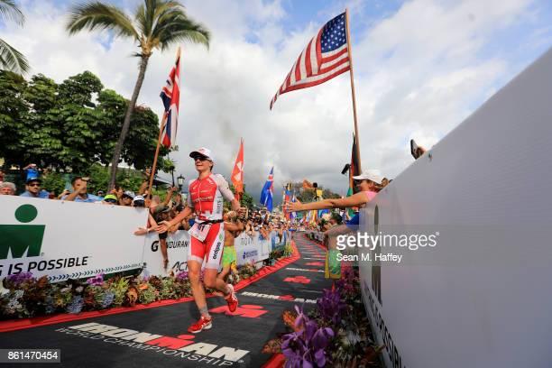 Daniela Ryf of Switzerland celebrates before crossing the finish line and winning the IRONMAN World Championship on October 14 2017 in Kailua Kona...