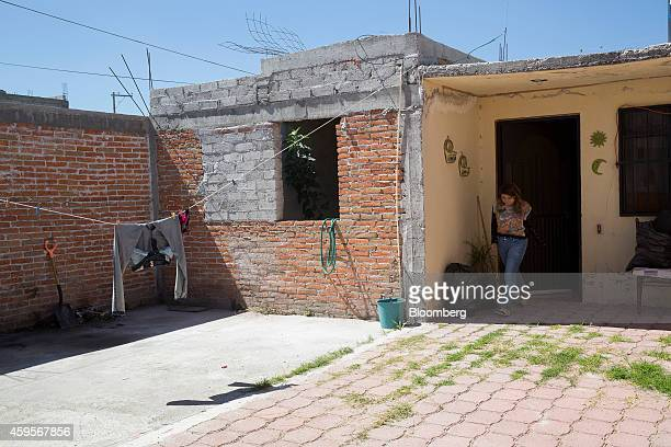 Daniela walks out of the home she shares with her mother Esmeralda Velazquez a machine operator at an auto suspension plant not pictured in Queretaro...