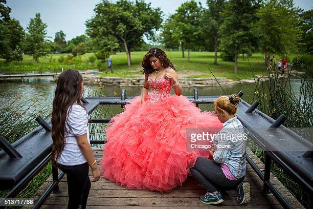 Daniela Zelaya gets help from her sister Skarleth and mother Odalis Zapata before posing for pictures in her quinceanera dress at Riis Park in the...