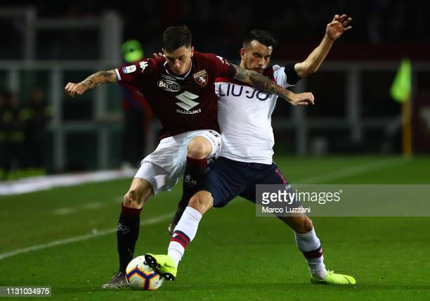 Daniele Baselli of Torino FC competes for the ball with Nicola Sansone of Bologna FC during the Serie A match between Torino FC and Bologna FC at...
