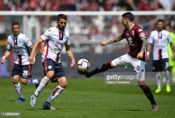 Daniele Baselli of Torino FC in action against Paolo Farago of Cagliari during the Serie A match between Torino FC and Cagliari at Stadio Olimpico di...