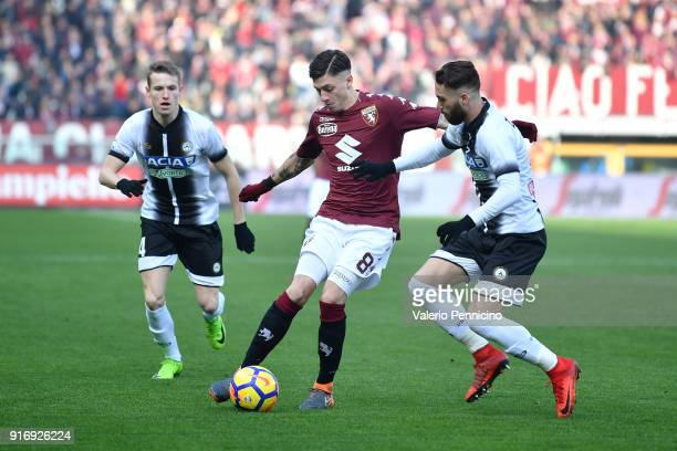 Daniele Baselli of Torino FC is challenged by Francesco Zampano of Udinese Calcio during the Serie A match between Torino FC and Udinese Calcio at...