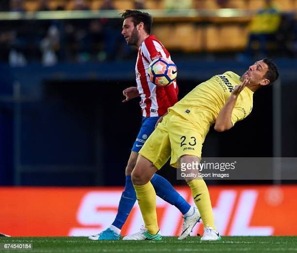 Daniele Bonera of Villarreal competes for the ball with Duje Cop of Real Sporting de Gijon during the La Liga match between Villarreal CF and Real...
