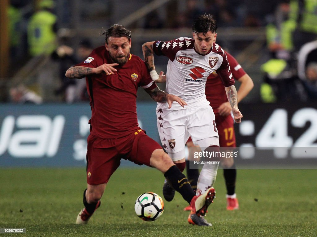 Daniele De Rossi of AS Roma competes for the ball with Daniele Baselli of Torino FC during the Serie A match between AS Roma and Torino FC at Stadio Olimpico on March 9, 2018 in Rome, Italy.