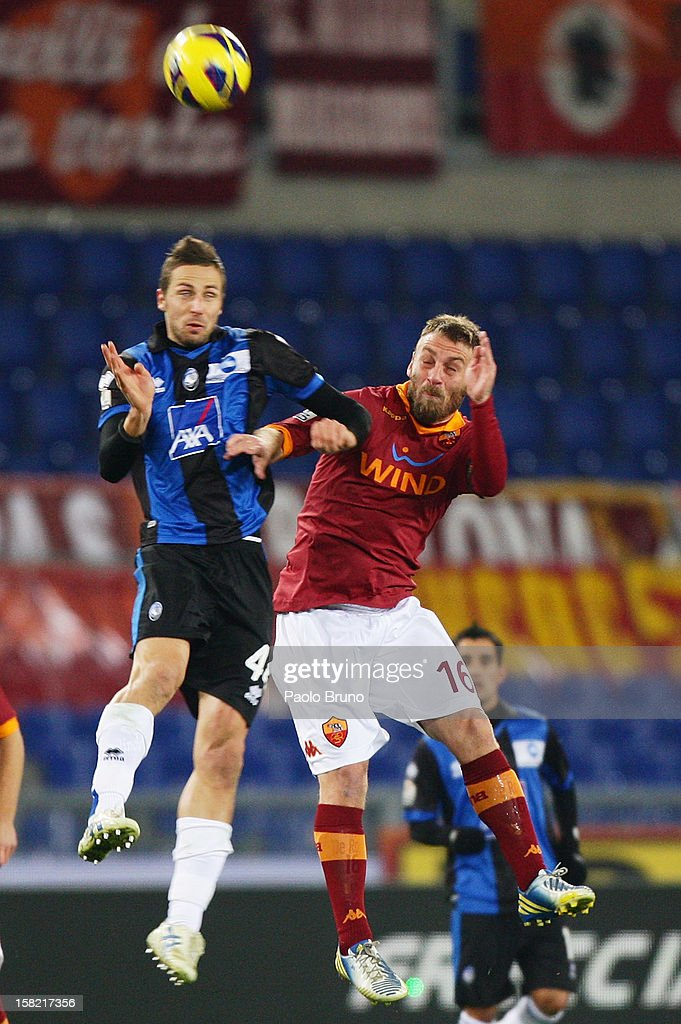 Daniele De Rossi (R) of AS Roma competes for the ball with Riccardo Cazzola of Atalanta BC during the TIM Cup match between AS Roma and Atalanta BC at Olimpico Stadium on December 11, 2012 in Rome, Italy.
