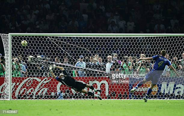 Daniele De Rossi of Italy scores a penalty kick past the dive of Fabien Barthez of France in a penalty shootout at the end the FIFA World Cup Germany...