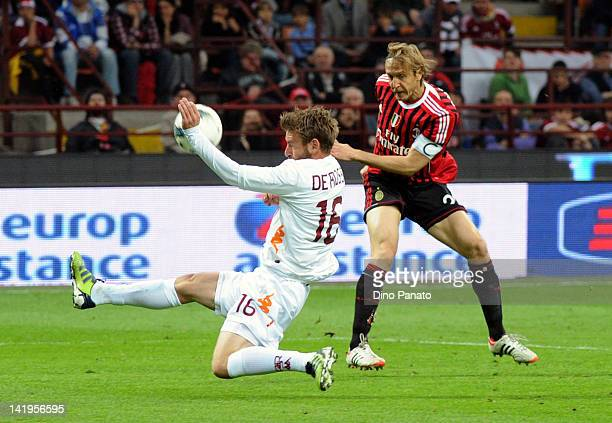 Daniele De Rossi of Roma blocks a shot from Massimo Ambrosini of Milan using his hand which resulted in a penalty kick for AC Milan during the Serie...