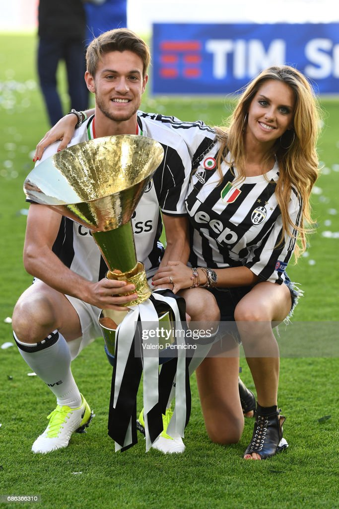 Daniele Rugani of Juventus FC and Michela Persico celebrate with the trophy after the beating FC Crotone 3-0 to win the Serie A Championships at the end of the Serie A match between Juventus FC and FC Crotone at Juventus Stadium on May 21, 2017 in Turin, Italy.