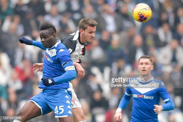 Daniele Rugani of Juventus jumps for the ball against Mario Balotelli of Brescia Calcio during the Serie A match between Juventus and Brescia Calcio...