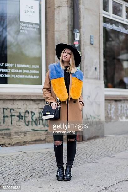 Daniele Sojka wearing a brown coat yellow blue fur scarf Steve Madden bag ripped denim jeans ankle boots hat during the MercedesBenz Fashion Week...