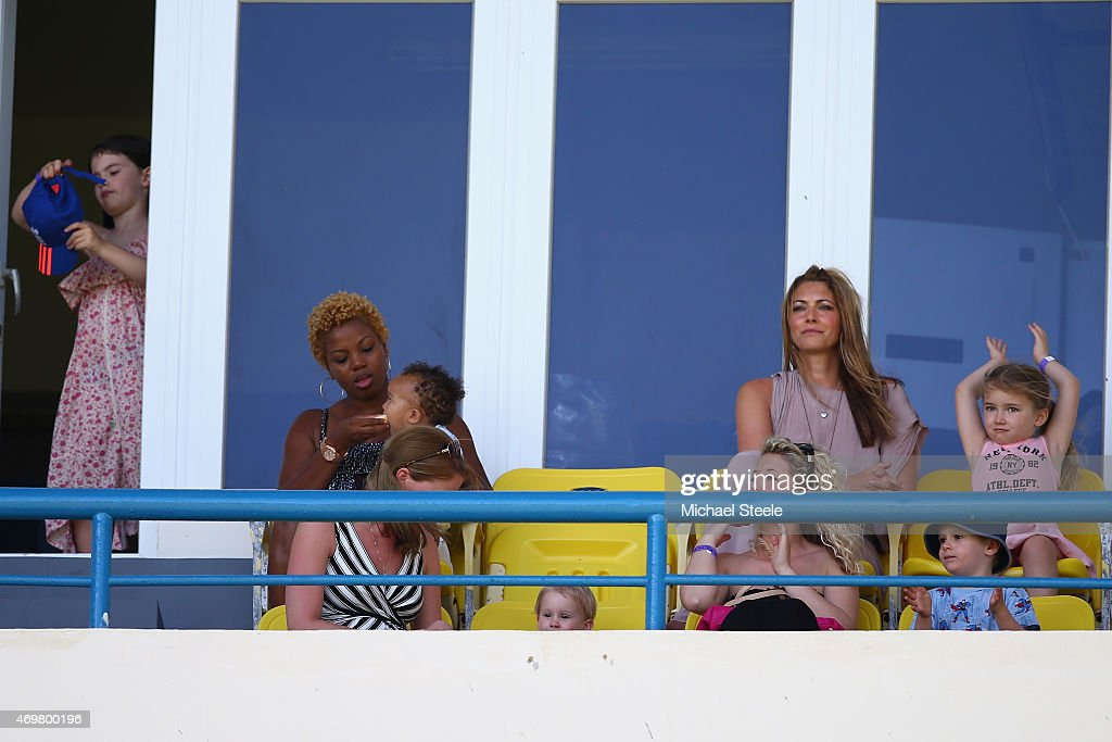 Daniella Anderson (2R) the wife of England cricketer James Anderson looks on alongside daughters Ruby Luxe (R) and Lola Rose (L) during day three of the 1st Test match between West Indies and England at the Sir Vivian Richards Stadium on April 15, 2015 in Antigua, Antigua and Barbuda.
