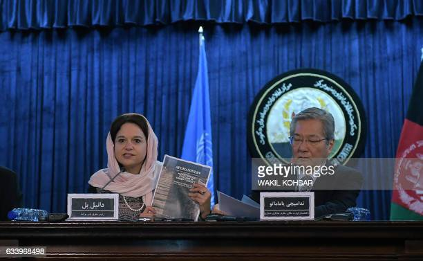 Danielle Bell director of human rights of UN Assistance Mission in Afghanistan holds up a copy of a report of civilian casualties next to Tadamichi...