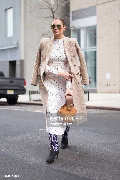 Danielle Bernstein is seen on the street attending SelfPortrait during New York Fashion Week wearing a long taupe coat with white polkadot dress on...