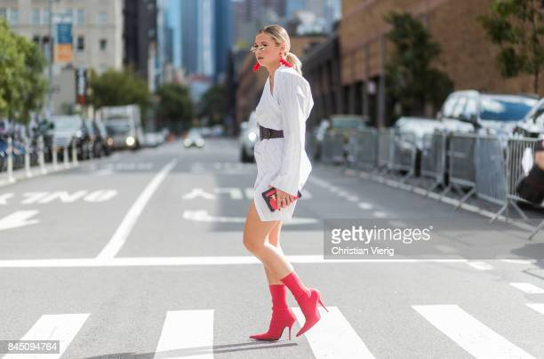 Danielle Bernstein wearing a white dress red sock boots earings seen in the streets of Manhattan outside Dion Lee during New York Fashion Week on...