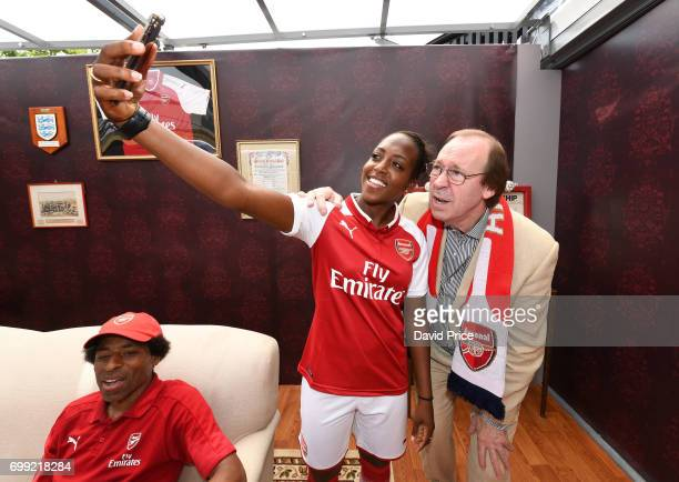 Danielle Carter of Arsenal Ladies poses with Former Arsenal player Charlie George on stage as they help introduce the new Arsenal Puma Home kit at...