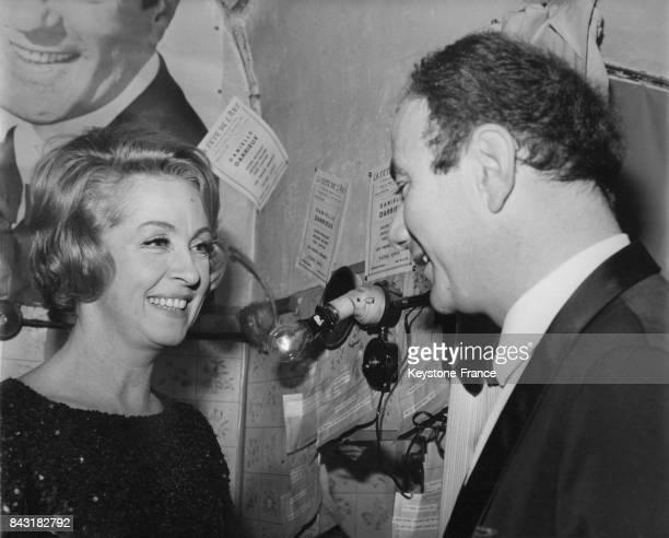 Danielle Darrieux après son récital est félicitée par Fernand Raynaud dans sa loge du cabaret 'La tête de l'art' à Paris France le 8 février 1968
