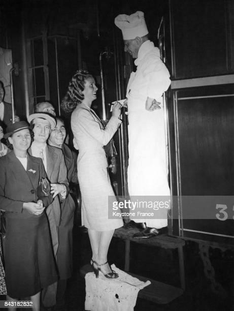 Danielle Darrieux en partance pour Budapest sur le marchepied du train signant un autographe au cuisinier du wagonrestaurant à la gare de l'Est à...