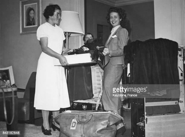 Danielle Darrieux en partance pour Hollywood faisant ses bagages aidée par son employée de maison dans son appartement à Paris France le 24 septembre...