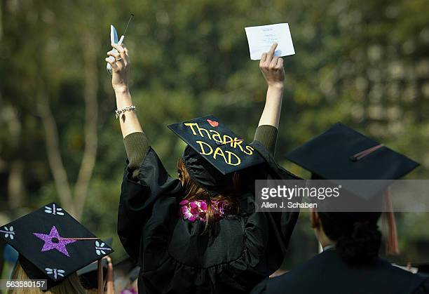Danielle Frey center who received her Social Ecology undergraduate degree displays her thanks to her father on her hat as she waves to her family...
