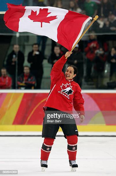 Danielle Goyette of Canada waves a Canadian flag to celebrate their 41 victory over Sweden to win the gold medal in women's ice hockey during Day 10...