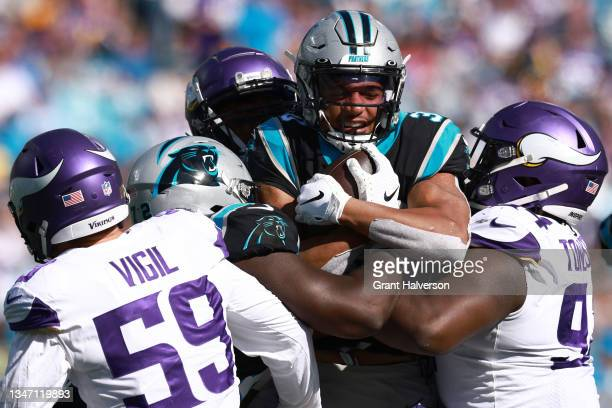 Danielle Hunter and Dalvin Tomlinson of the Minnesota Vikings tackle Chuba Hubbard of the Carolina Panthers during the third quarter at Bank of...