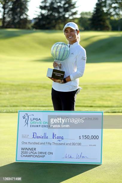Danielle Kang celebrates with the trophy and is presented the winner's check on the 18th green after her 7 under par final round victory of the LPGA...