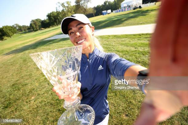 "Danielle Kang imitates a ""selfie"" as she poses with the trophy after winning the Marathon LPGA Classic during the final round at Highland Meadows..."