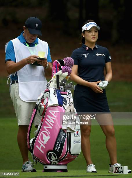 Danielle Kang of South Korea stands with her caddie on the 18th hole during the first round of the 2018 US Women's Open at Shoal Creek on May 31 2018...