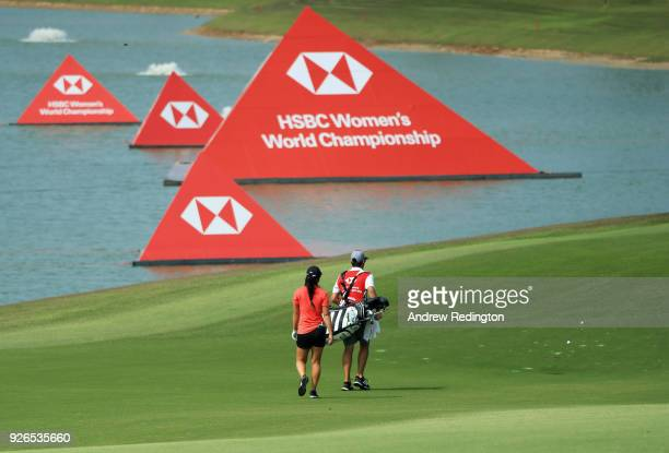 Danielle Kang of the United States walks with her caddie on the fifth hole during round three of the HSBC Women's World Championship at Sentosa Golf...