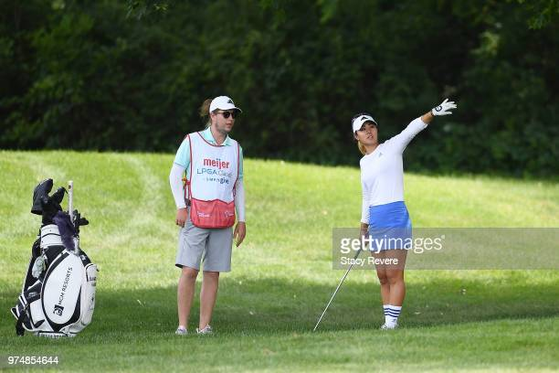 Danielle Kang speaks with her caddie on the first hole during the first round of the Meijer LPGA Classic for Simply Give at Blythefield Country Club...
