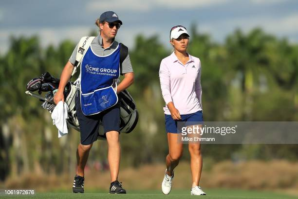 Danielle Kang talks with her caddie as she walks up the 18th fairway during the first round of the CME Group Tour Championship at Tiburon Golf Club...