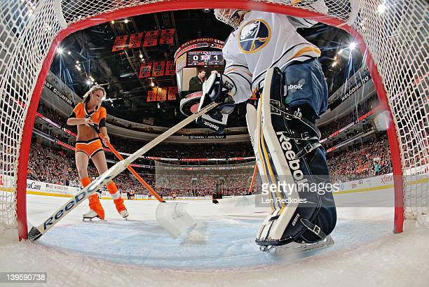 Danielle Marina of the Philadelphia Flyers ice girls cleans the ice during a stoppage in play with goaltender Jhonas Enroth of the Buffalo Sabres on...