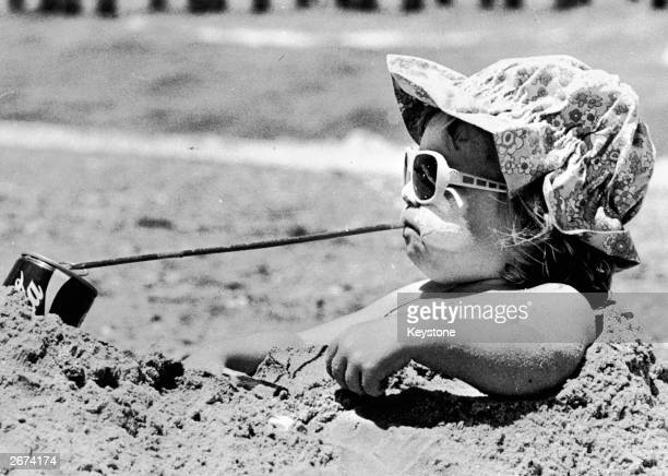 Danielle Martin enjoying a cold drink as she sits in a sand hole on the beach near Melbourne
