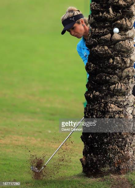 Danielle Montgomery of England plays her third shot from behind a palm tree at the par 4, 9th hole during the second round of the 2012 Omega Dubai...