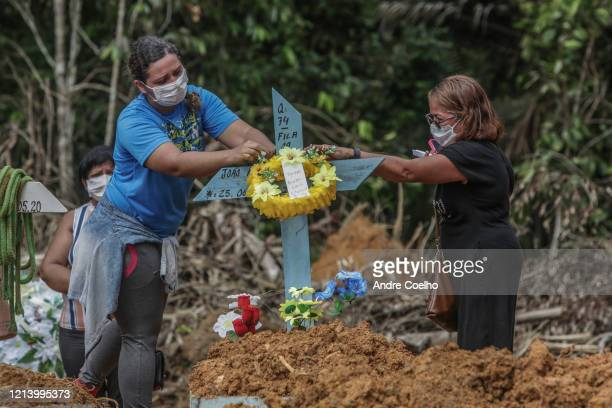 Danielle Mota da Silva and her mother put flowers after the burial of her father Joao Ricardo at the Parque Taruma cemetery on May 19 2020 in Manaus...