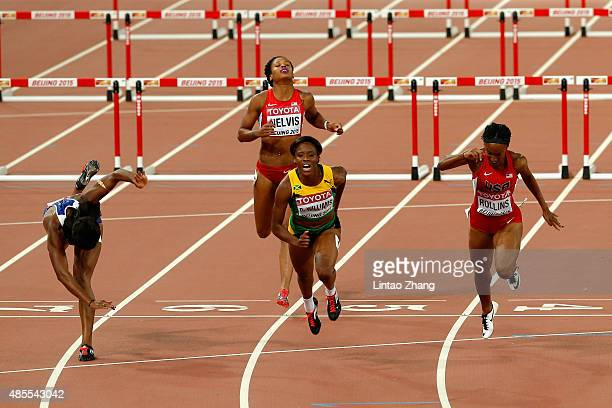 Danielle Williams of Jamaica crosses the finish line to win gold in the Women's 100 metres hurdles final as Tiffany Porter of Great Britain falls...